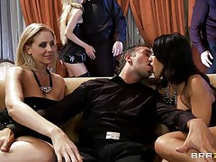 A blond and a dark brown are rubbing a guy's crotch whilst sitting on a couch. They pull out his cock and start to suck it, each waiting her turn. Another dick enters the scene and the dark brown goes to blow it.