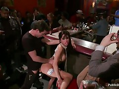 Gia DiMarco is on a rope leash, getting fucked in the booty right in the centre of the bar while the patrons watch. This babe continuously thanks James Deen for fucking her ass. Then she's on the floor, getting fingered by a woman, squirting all over. This babe mops up the mess with Gia's hair, then fists her.